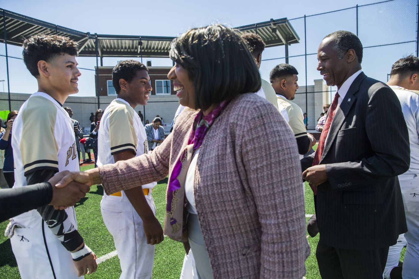 U.S. Secretary of Housing and Urban Development Ben Carson, center, and his wife, Candy Carson, meet youth baseball players while they take a tour of the Dallas Housing Authority's Major League Baseball Youth Academy. (Ashley Landis/The Dallas Morning News)
