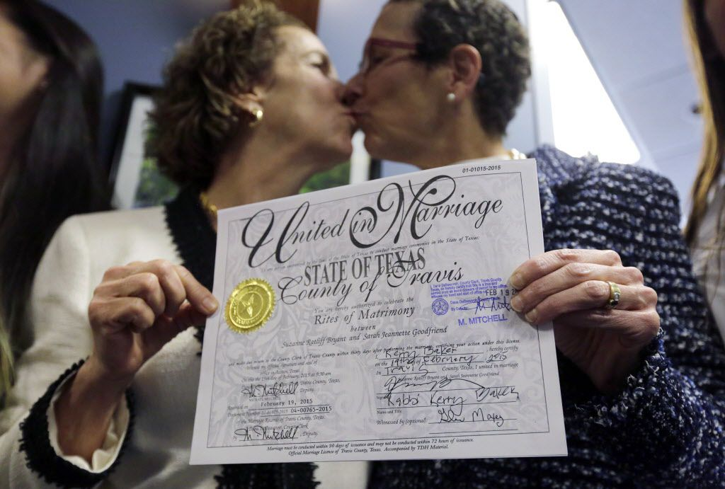 Suzanne Bryant, left, and Sarah Goodfriend, right, exchange a kiss as they pose for a portrait with their marriage license following a news conference, Thursday, Feb. 19, 2015, in Austin, Texas. Despite Texas' longstanding ban on gay marriage, the same-sex couple married Thursday immediately after being granted a marriage license under a one-time court order issued for medical reasons. (AP Photo/Eric Gay)