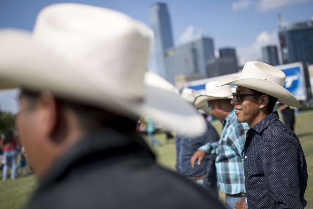 Jose Mendez (right), of Dallas watches the performance on stage during La Grande 107.5 Fiestas Patrias at Reunion Park on Sept. 4, 2016 in Dallas.