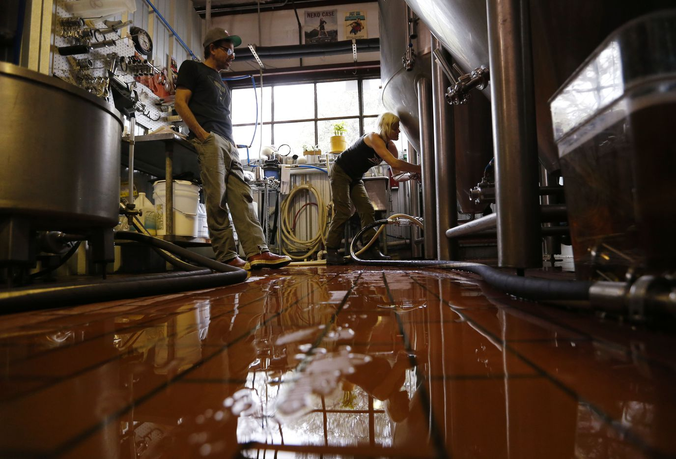 """Brewer Brian """"Swifty"""" Peters talks to Kim Mizner as she cleans out a fermenter at Austin Beer Garden Brewing Company."""