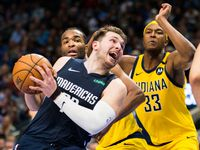FILE - Mavericks guard Luka Doncic (77) is fouled by Pacers forward T.J. Warren (1) during the fourth quarter of a game on Sunday, March 8, 2020, at American Airlines Center in Dallas.