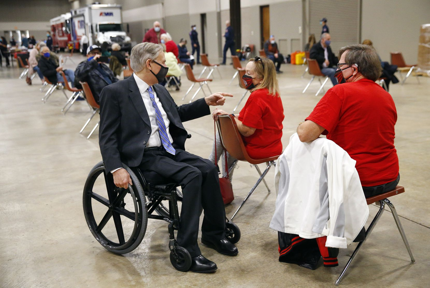Texas Governor Greg Abbott (left visits with Michael and Sara Cramer of Arlington in a waiting area after receiving their COVID-19 shots at a mass COVID-19 vaccination site at the Esports Stadium Arlington & Expo Center in Arlington, Texas, Monday, January 11, 2021. (Tom Fox/The Dallas Morning News)
