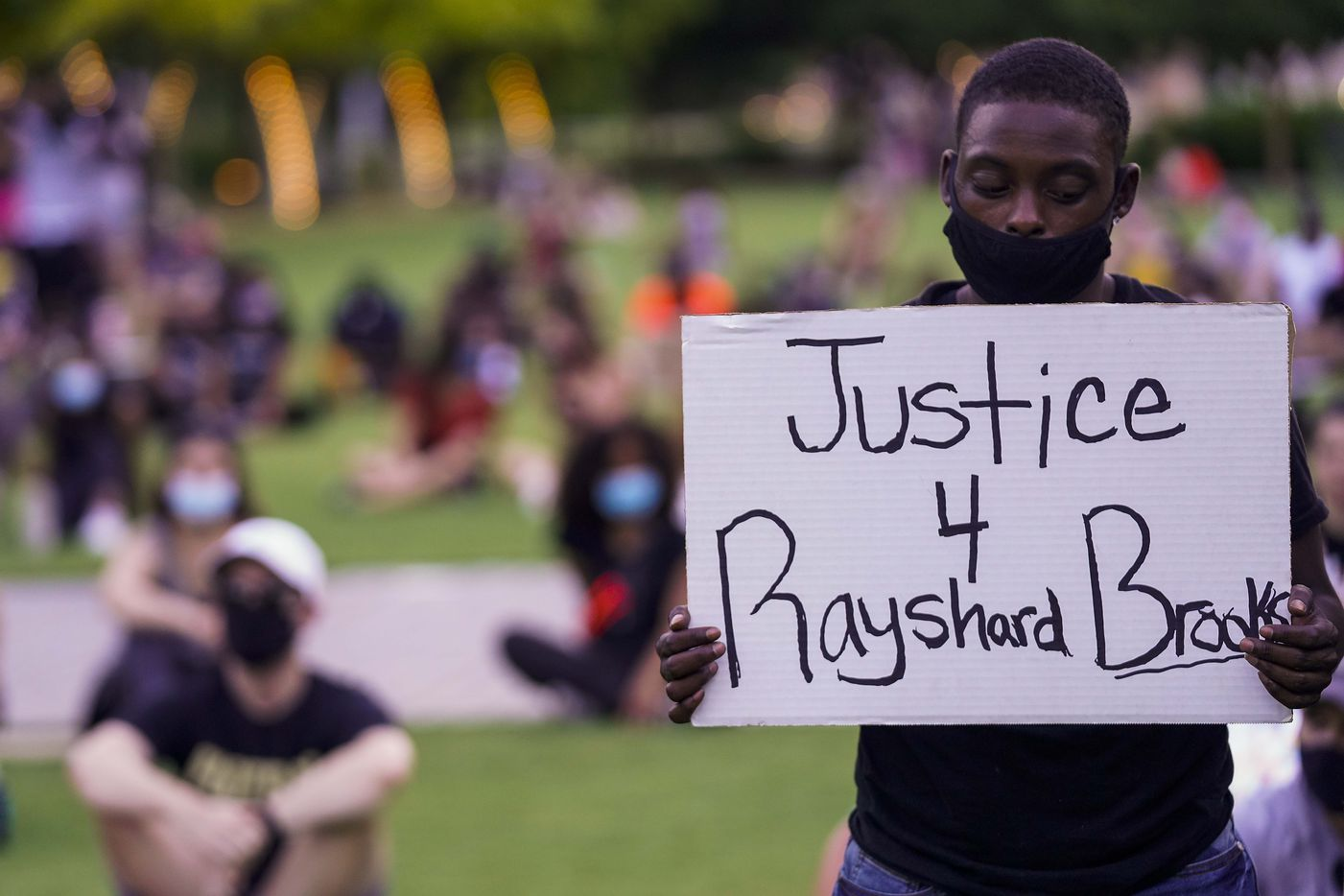 A man holds a sign calling for justice for Rayshard Brooks during rally for Juneteenth in the background at Klyde Warren Park on Friday, June 19, 2020, in Dallas.