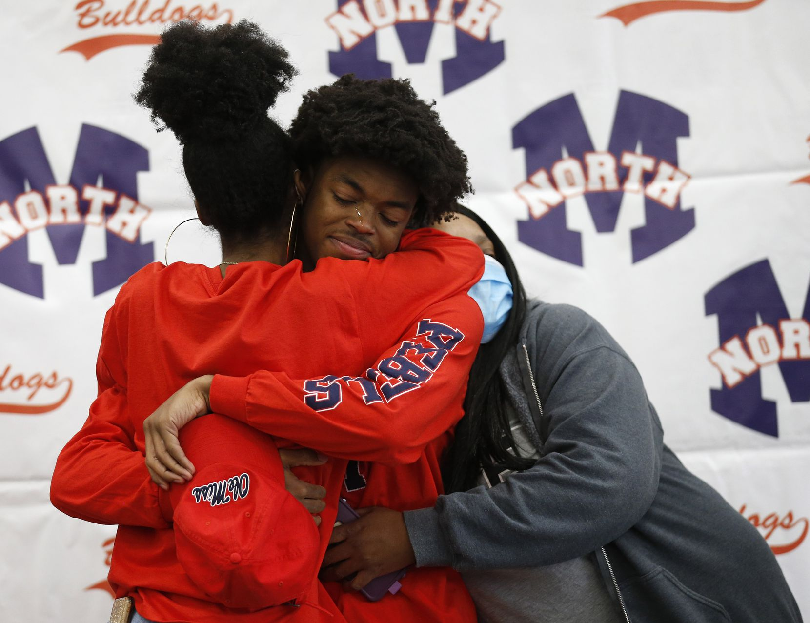 McKinney North wide receiver J.J. Henry gets hugs from his sister Jai-lynn Henry (left) and his aunt Christie Hollins after signing his letter of intent to play for the University of Mississippi during a signing day ceremony at McKinney North High School on Wednesday, December 16, 2020 in McKinney, Texas. (Vernon Bryant/The Dallas Morning News)