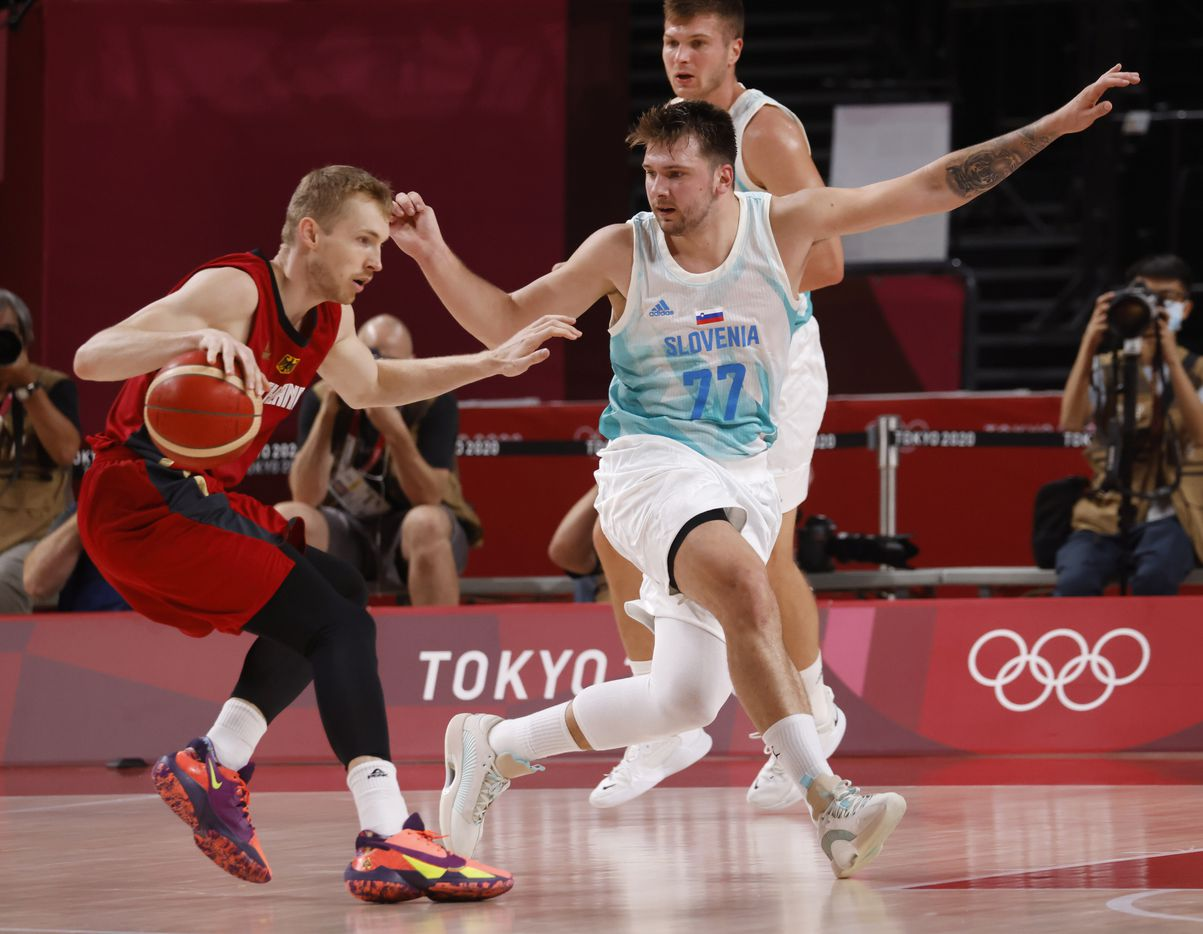 Slovenia's Luka Doncic (77) defends as Germany's Niels Giffey (5) dribbles during the first half of play of a quarter final basketball game at the postponed 2020 Tokyo Olympics at Saitama Super Arena, on Tuesday, August 3, 2021, in Saitama, Japan. (Vernon Bryant/The Dallas Morning News)