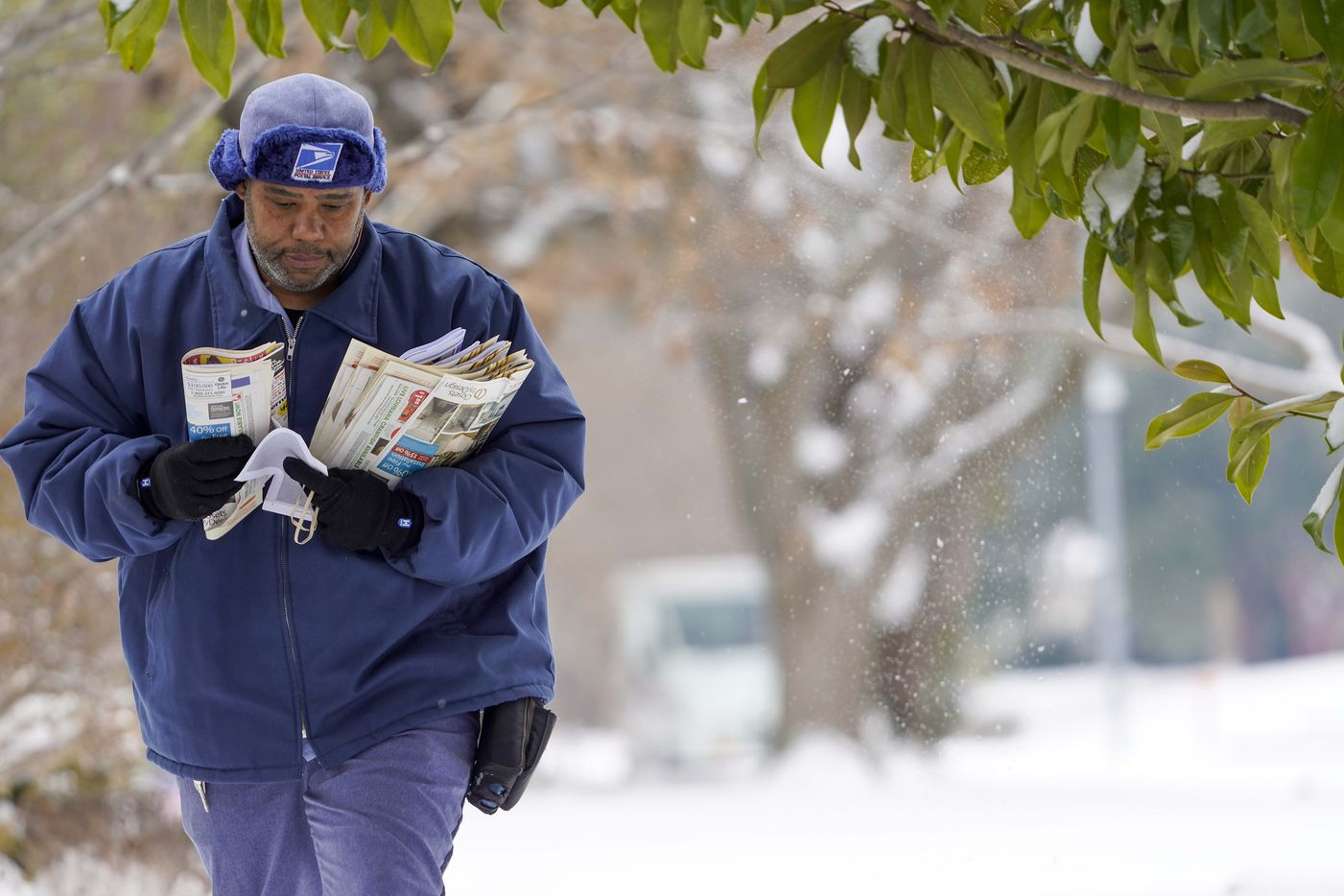 USPS mail carrier RayShawn Riley delivers mail to a snow covered neighborhood after a second winter storm brought more snow and continued freezing temperatures to North Texas on Wednesday, Feb. 17, 2021, in Richardson.