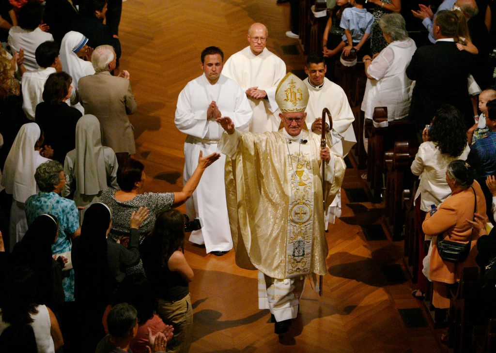 "In this July 7, 2006, file photo, Bishop Charles Grahmann of the Catholic Dioceses of Dallas waves to his congregation as he exits the Cathedral Shrine of the Virgin of Guadalupe  after celebrating a ""Triple Jubilee"" Mass to commemorate his 75th birthday. The Catholic Diocese of Dallas says that the Most Rev. Charles Grahmann, whose 17-year tenure as bishop of the diocese was marred by one of the first church sex abuse scandals to explode into public view, has died at age 87."