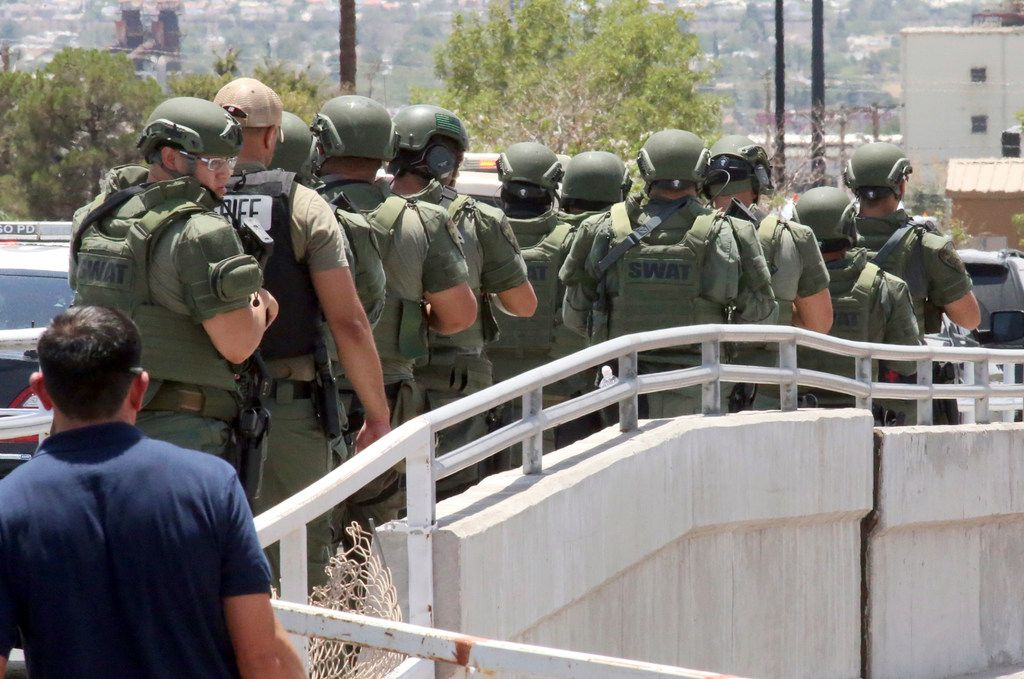 Law enforcement officers make their way along a walkway to the scene of a shooting at a shopping mall in El Paso, Texas, on Saturday, Aug. 3, 2019.   Several people were killed in the shooting Saturday in a busy shopping area in the Texas border town.