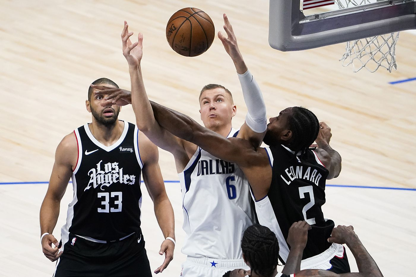 Dallas Mavericks center Kristaps Porzingis (6) fight for a rebound against LA Clippers forward Kawhi Leonard (2) and forward Nicolas Batum (33) during the first quarter of an NBA playoff basketball game at American Airlines Center on Sunday, May 30, 2021, in Dallas. (Smiley N. Pool/The Dallas Morning News)