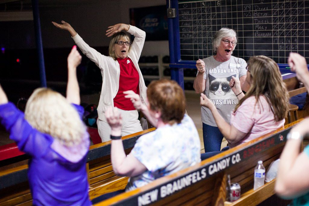 Teams take a dance break to sing along during a game of ninepin cosmic bowling at Solms Bowling Club in New Braunfels. (Julysa Sosa/San Antonio Express-News via AP)