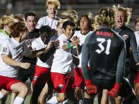 Rockwall-Heath senior defender Oscar Perales, center, is mobbed by teammates after scoring the game winning goal in a shootout after a boys soccer Class 6A state semifinal against Allen at Mesquite Memorial Stadium in Mesquite, Tuesday, April 13, 2021. Rockwall-Heath won 3-1 in a shootout.