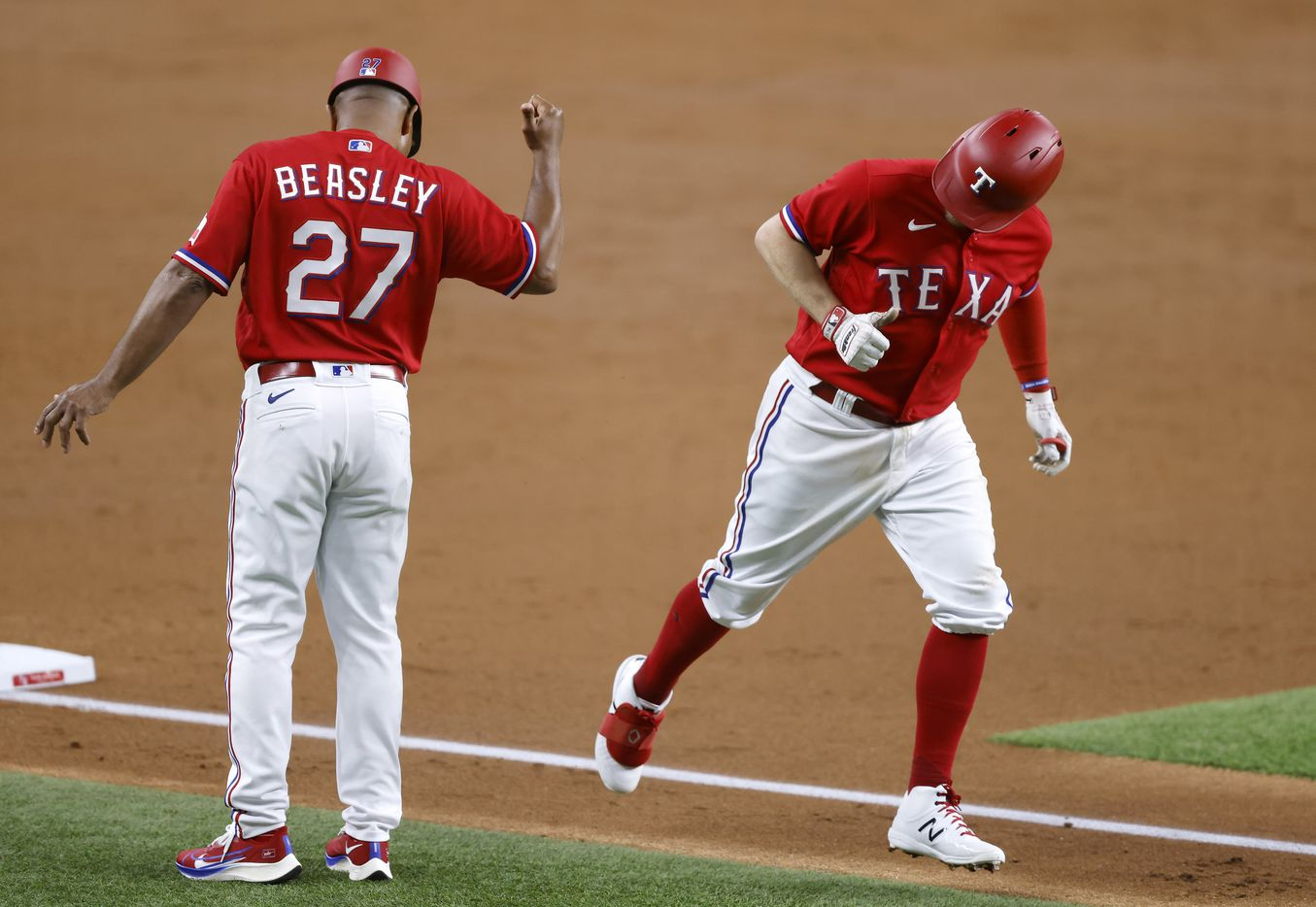 Texas Rangers batter Brock Holt (16) gives third base coach Tony Beasley (27) a thumbs up after hitting a solo home run against the Houston Astros in the third inning at Globe Life Field in Arlington, Texas, Friday, May 21, 2009. (Tom Fox/The Dallas Morning News)