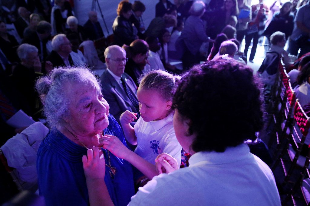 Holocaust survivor Rose Blum (left) is dedicated with a pin by Anne Frank Elementary students Iv Jackson (center), 10, and Maya Molina (right), 11, at the groundbreaking ceremony for the new Dallas Holocaust and Human Rights Museum in the West End of Dallas Tuesday October 10, 2017. Blue was presented when the museum first opened in Dallas. The ceremony also honored other local Dallas-Fort Worth Holocaust survivors in attendance. At 300 North Houston Street the new museum will be 51,000 square feet and set to open in the summer of 2019.