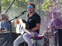 Eli Young Band performs for a crowd in their cars as they tune into an FM radio station for the live music on June 4, 2020 in Tundra Lot B at Globe Life Field in Arlington, Texas.