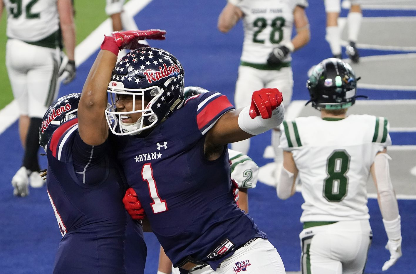 Denton Ryan wide receiver Ja'Tavion Sanders (1) celebrates with teammate Jay Sheppard (8) after catching a touchdown pass from quarterback Seth Henigan past Cedar Park defensive back Casyn Wiesenhutter (8) during the second half of the Class 5A Division I state football championship game at AT&T Stadium on Friday, Jan. 15, 2021, in Arlington, Texas. Ryan won the game 59-14. (Smiley N. Pool/The Dallas Morning News)