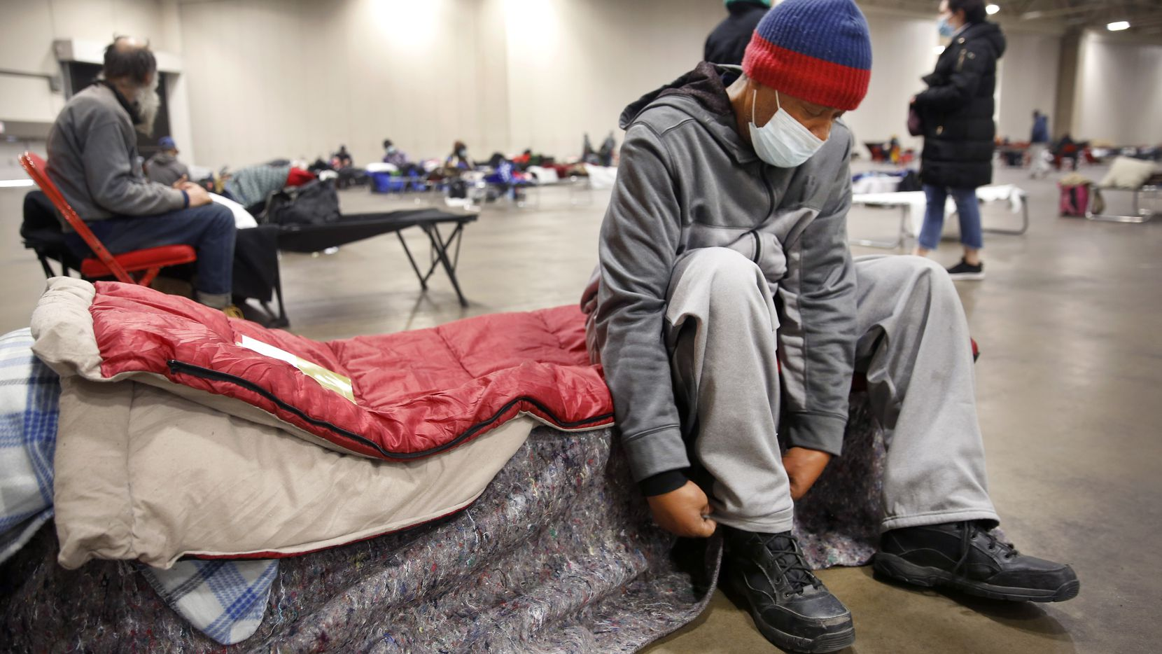 Pierre Scott, a 59 year-old guest and volunteer at a warming center run by OurCalling, changed socks on his socially-distanced cot at the Kay Bailey Hutchison Convention Center in Dallas, Tuesday, February 16, 2021. Scott like a lot of other folks, found refuge from the overnight sub-zero temperatures. (Tom Fox/The Dallas Morning News)