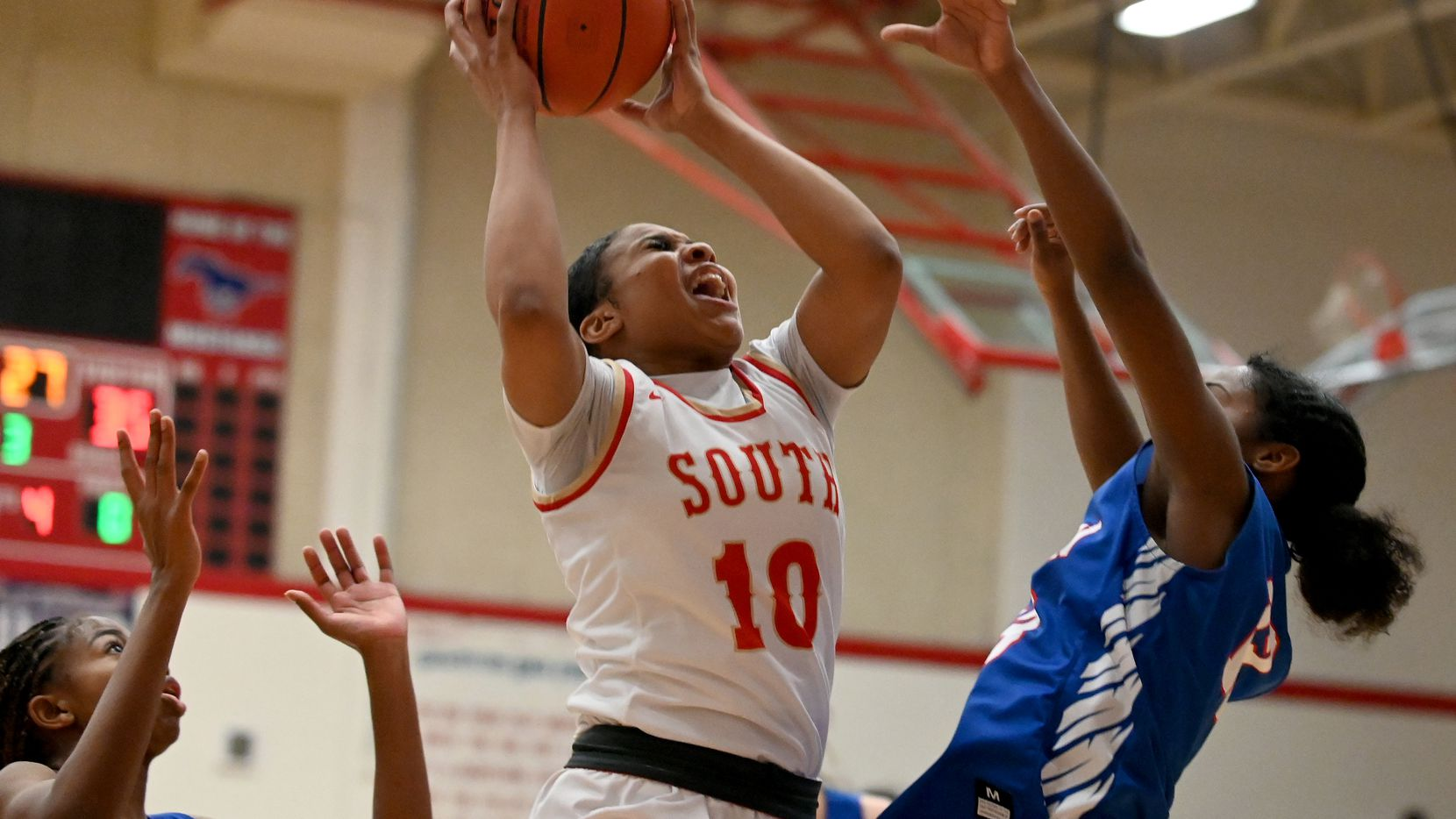 South Grand Prairie's Victoria Dixon (10) grabs a rebound between Allen's Alicia Mills and Zoe Jackson in the second half of a Class 6A area-round playoff game Saturday. SGP won 61-45. (Matt Strasen/Special Contributor)