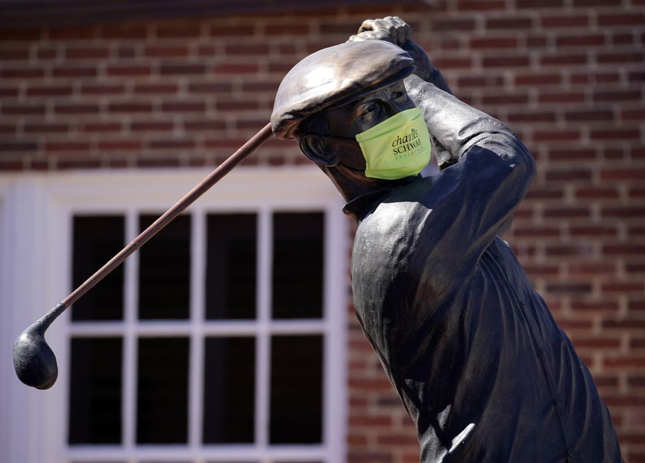 In the wake of COVID-19, the Ben Hogan statue, which greets golfers to the course, bears a mask at the Colonial Country Club in Fort Worth, Wednesday, June 10, 2020.
