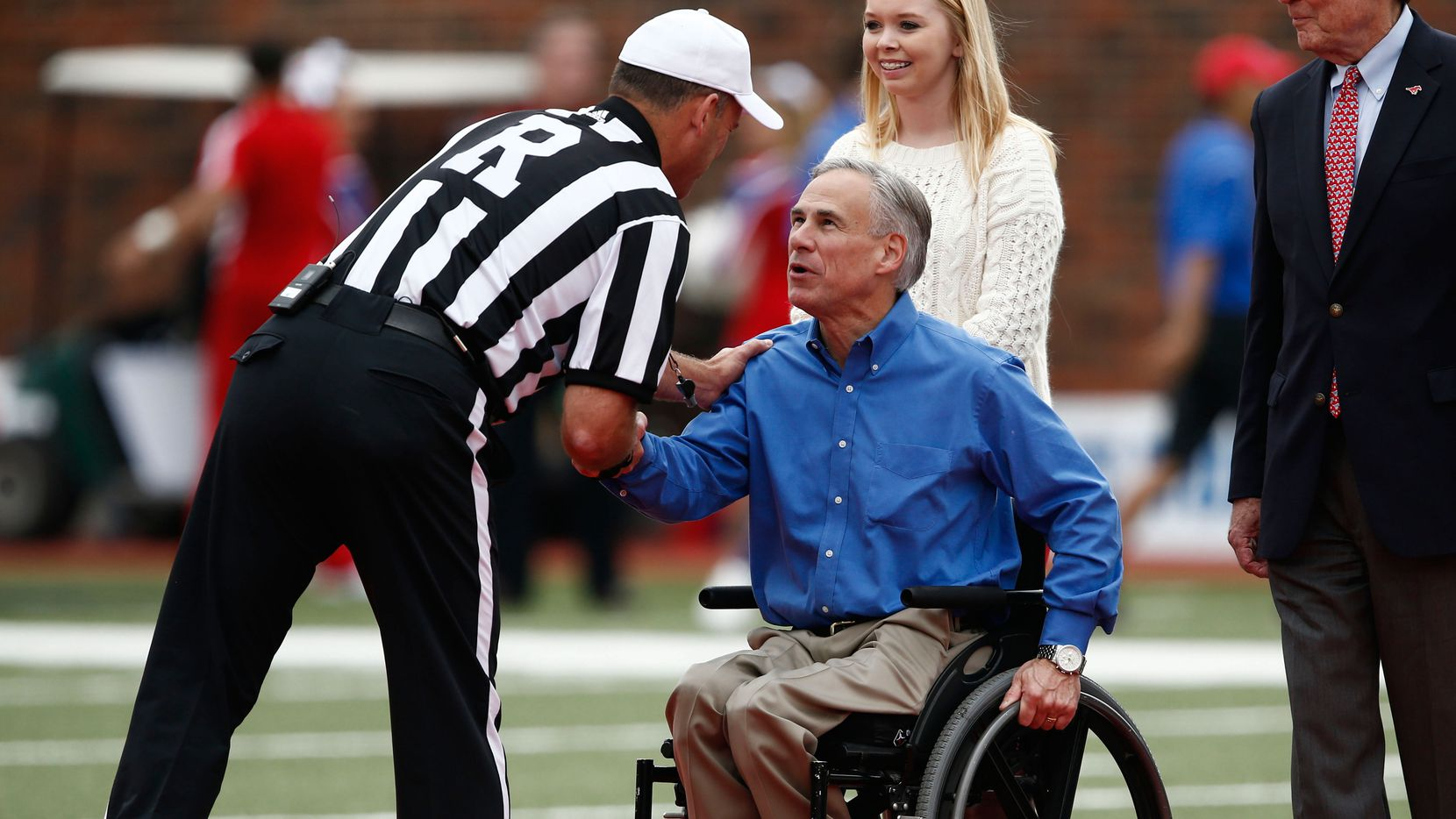 Greg Abbott, then attorney general of Texas, greets an official at midfield before the college football game between the Southern Methodist Mustangs and the Temple Owls at Gerald J. Ford Stadium in Dallas on Oct. 26, 2013.