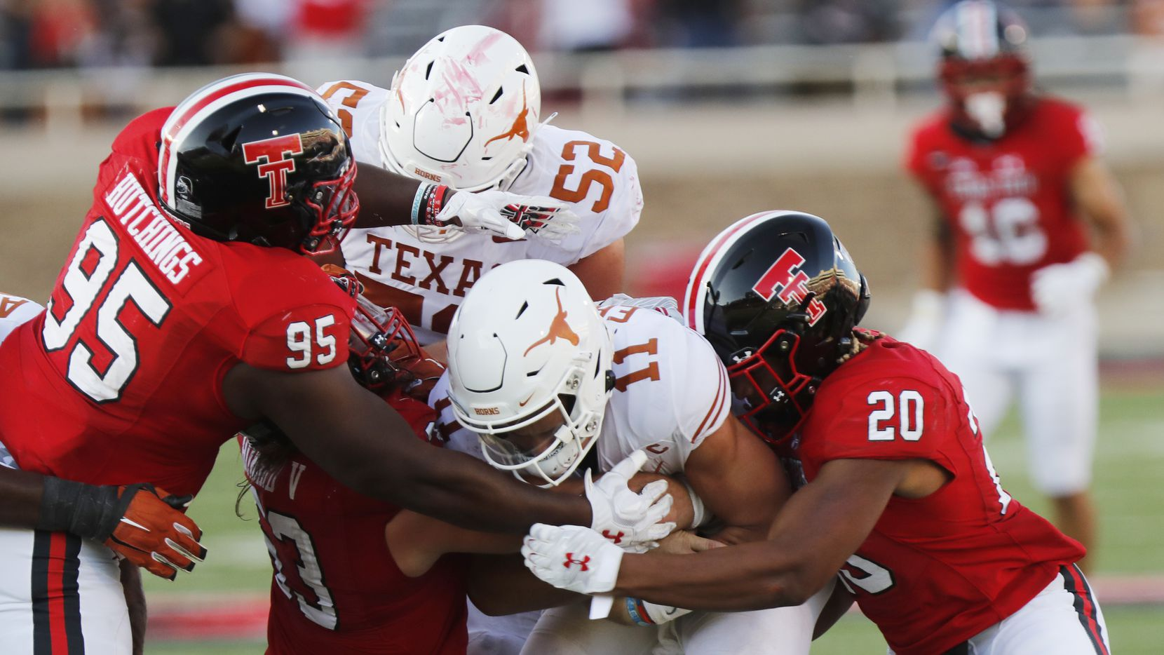 Texas Tech defensive lineman Jaylon Hutchings and linebacker Kosi Eldridge tackle Texas quarterback Sam Ehlinger during the second half of an NCAA college football game against Texas Tech, Saturday Sept. 26, 2020, in Lubbock, Texas. (AP Photo/Mark Rogers)