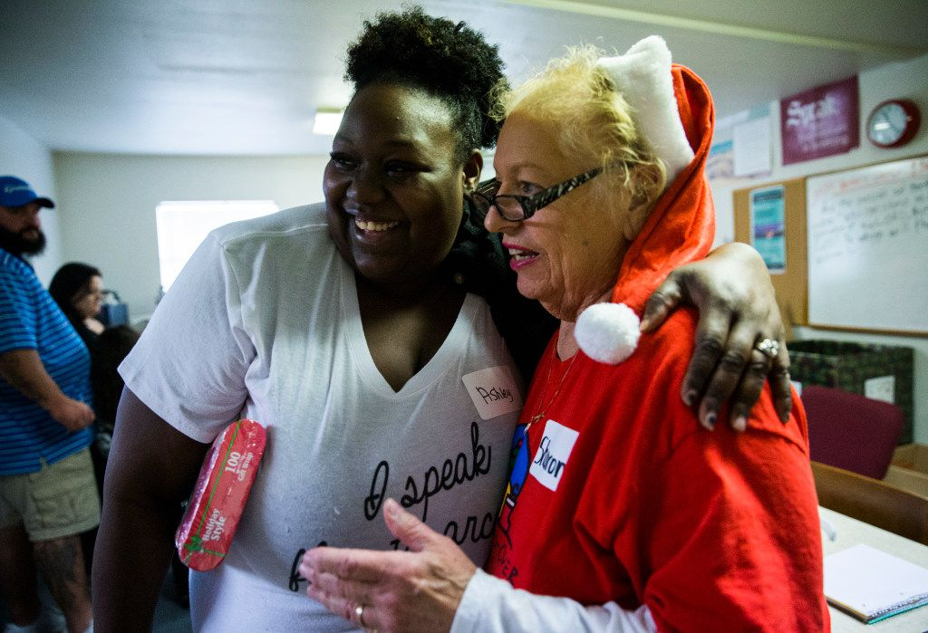Ashley Fuller-James and volunteer Sharon Screws hug during The Big Christmas Do-Over in Rowlett.