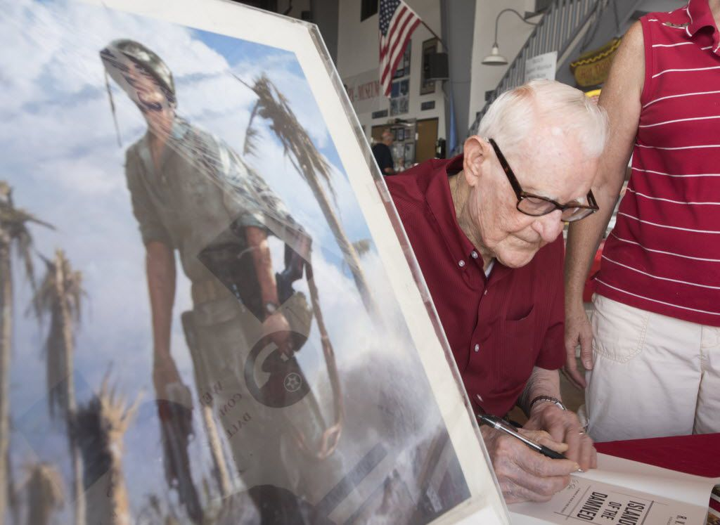 R.V. Burgin, author of Islands of the Damned: A Marine at War in the Pacific, signed copies of his book during the Commemorative Air Force DFW Warbirds on Parade event at Lancaster Airport in 2015.