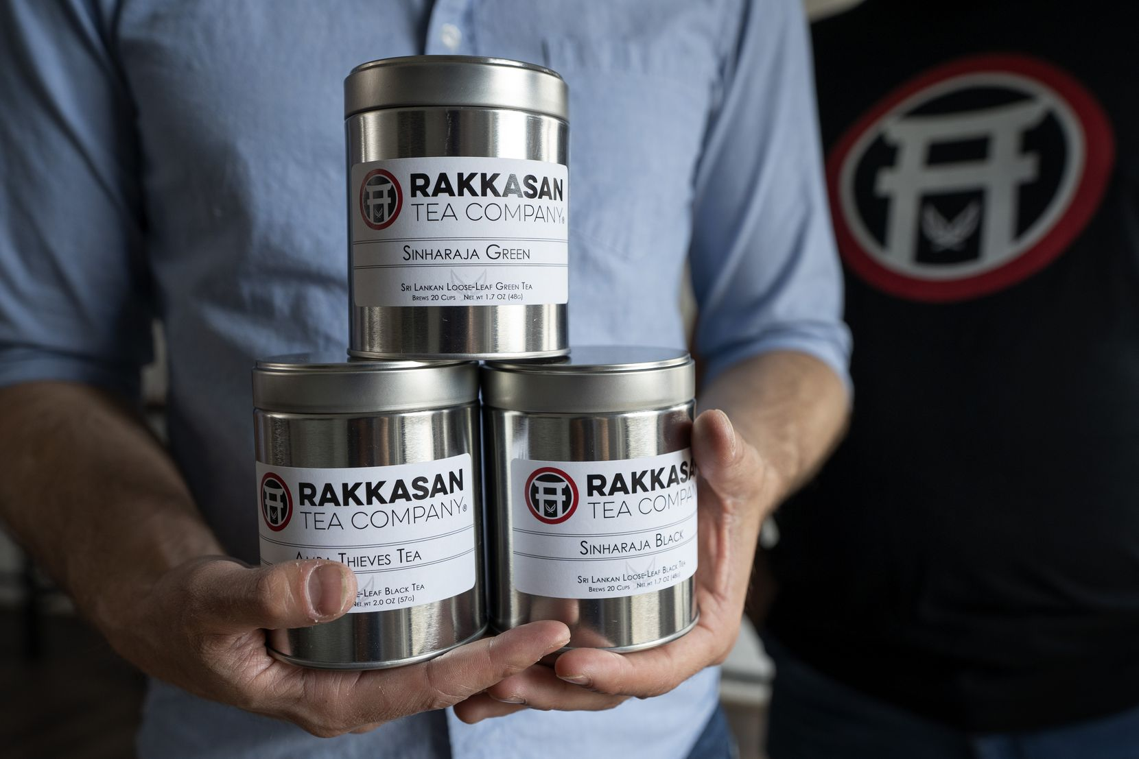 Brandon Friedman, CEO of Rakkasan Tea, holds canisters of loose-leaf tea at the company's new brick-and-mortar store near Hall Street and Ross Avenue in Dallas.