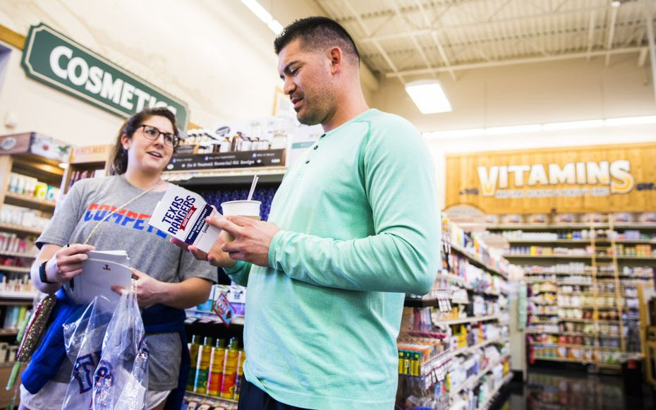 Texas Rangers nutritionist Stephanie Fernandes gives a restaurant guide to starting pitcher Eddie Gamboa (78) while they shop for groceries at Sprouts before a spring training cooking class at the team's training facility on Thursday, February 23, 2017 in Surprise, Arizona. (Ashley Landis/The Dallas Morning News)