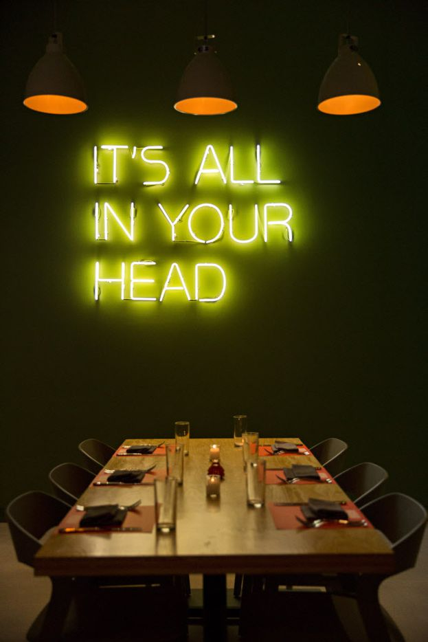 A table basks in the glow of a neon sign and overhead lights at Americano.