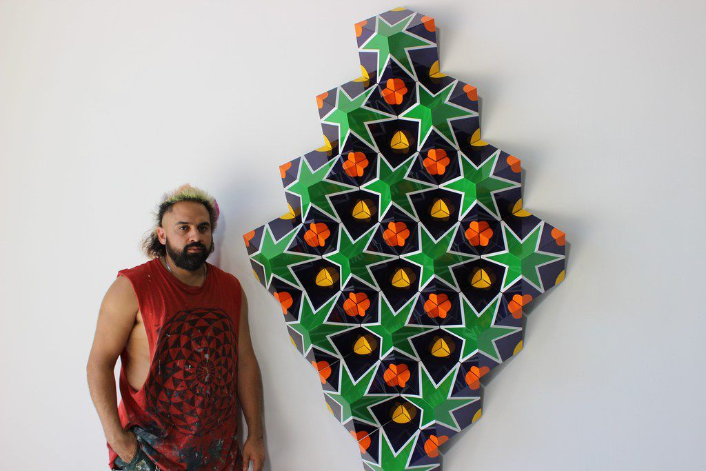 Dallas artist Ricardo Paniagua poses next to one of his recent works.