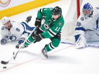 Dallas Stars center Andrew Cogliano (11) swings around the goal for an attempted, and missed, shot past Tampa Bay Lightning goaltender Andrei Vasilevskiy (88) as Tampa Bay Lightning center Tyler Johnson (9) falls to the ice during the first period of a NHL matchup between the Dallas Stars and the Tampa Bay Lightning on Monday, Jan. 27, 2020 at American Airlines Center in Dallas.