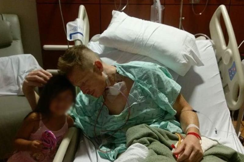 Gregory Epley Jr. in the hospital. His visitor's face was blurred at the family's request to protect her identity. (GoFundMe)