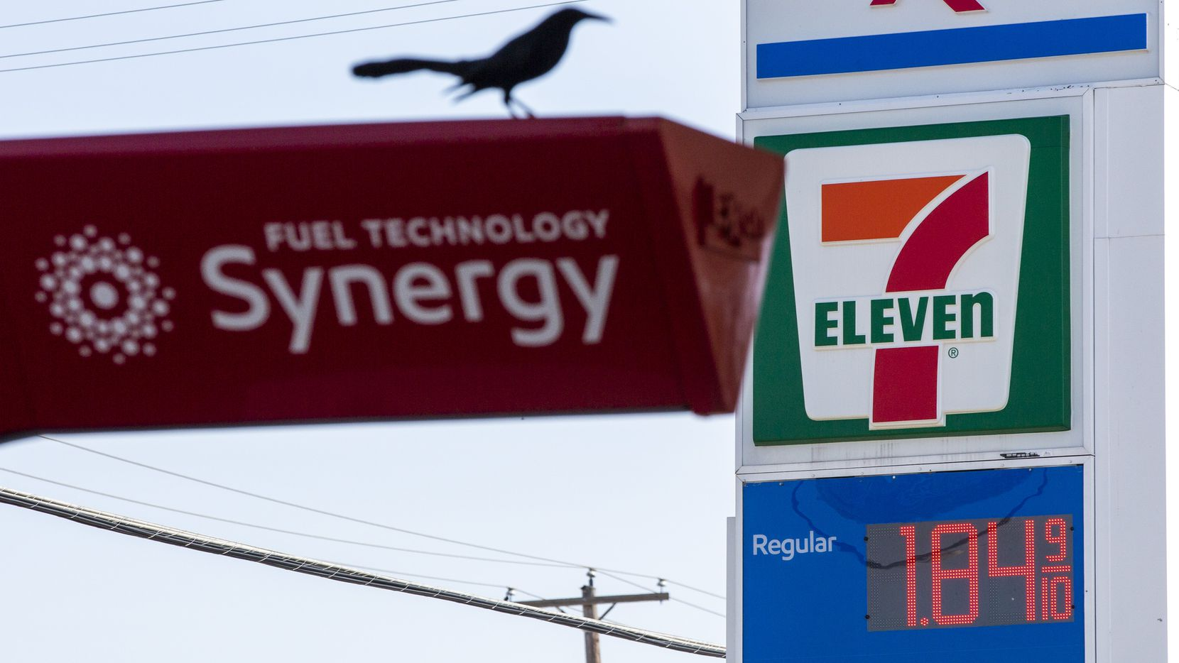 Signs advertise low gas prices at an Exxon gas station in Dallas on Thursday, March 12, 2020.