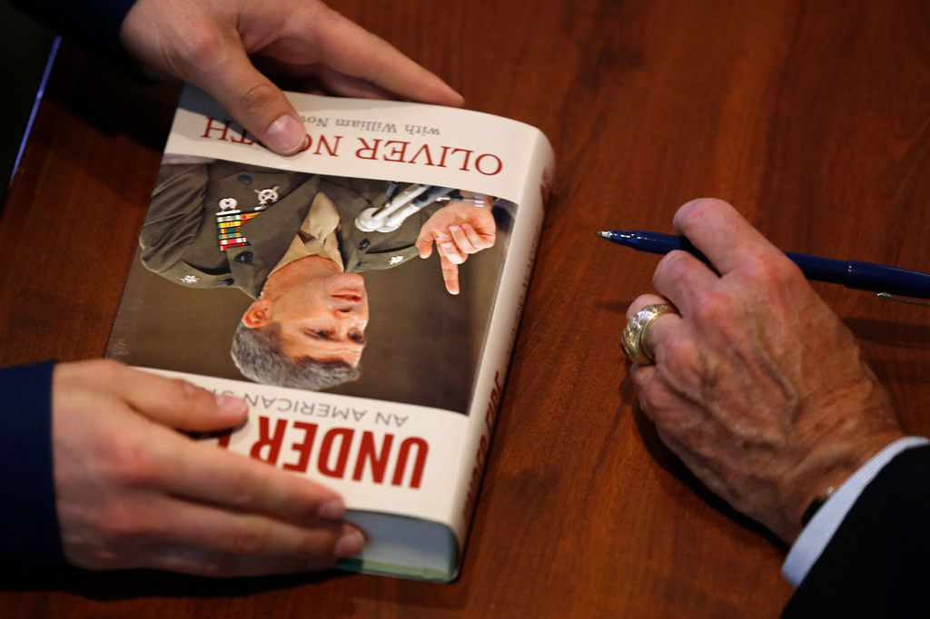 """Lt. Col. Oliver North, the incoming president of the National Rifle Association, right, signs his book """"Under Fire: An American Story"""" at Fellowship Church in Grapevine, Texas, Sunday, May 27, 2018. (Jae S. Lee/The Dallas Morning News)"""