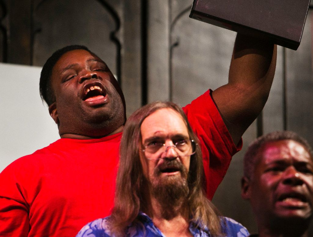 Steven Joiner raises his song book while he sings during the Dallas Street Choir performance at the Munger Place Church.