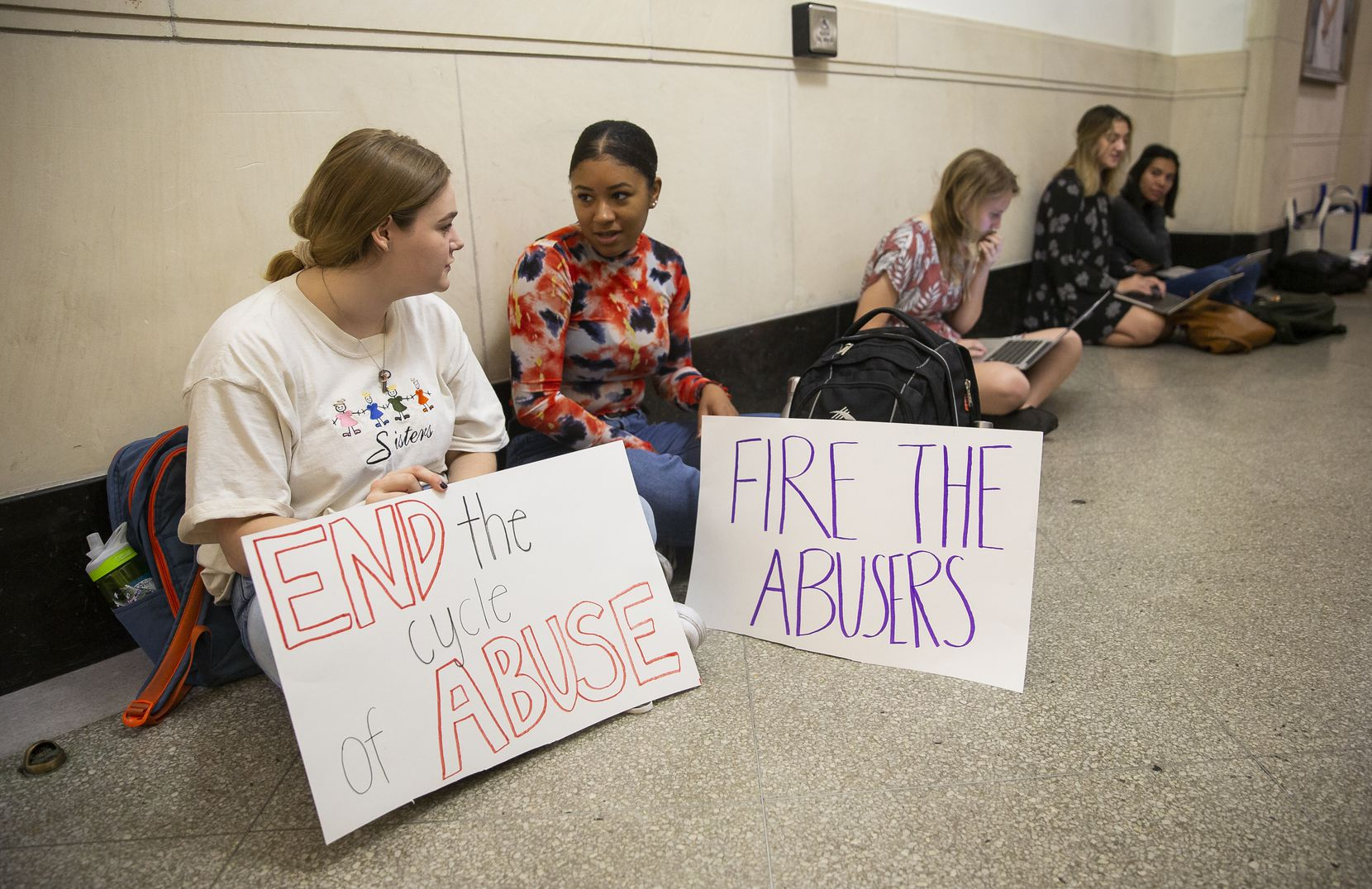 "UT Austin juniors Ky Higdon (left) and Courtney LeBlanc hold signs outside of Executive Vice President and Provost Maurie McInnis' office on Nov. 20, 2019 in Austin. ""We're not gonna let them get away with them not putting us first,"" LeBlanc said."