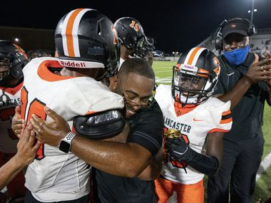 Lancaster head coach Leon Paul is congratulated by running back Isaiah Broadway (20) and wide receiver Ti'Erick Martin (13) after notching his first ever win as a head coach in a high school football game against Skyline on Friday, Sept. 3, 2021 at Forester Field in Dallas. Paul was previously an assistant coach at Duncanville.