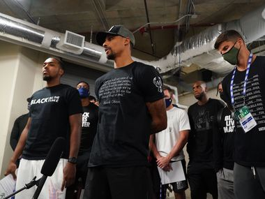 ORLANDO, FL - AUGUST 26: Sterling Brown (far left) and George Hill (2nd from left) of the Milwaukee Bucks reads a statement to the media on August 26, 2020 at AdventHealth Arena at ESPN Wide World of Sports Complex in Orlando, Florida.