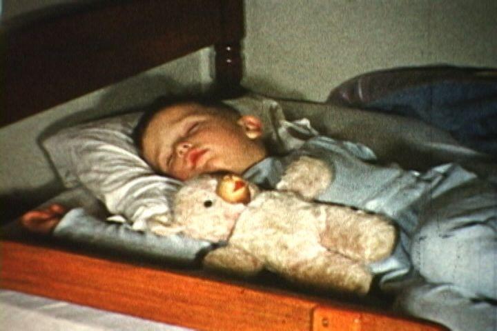 Baby Ron Siebler sleeps with his teddy bear on Christmas Eve, 1954.
