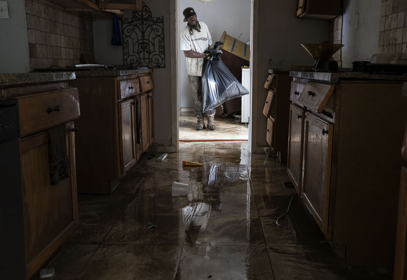 Ron Hardy helped clean out  Michael Boyd's flooded  home on Wednesday, Aug. 30  in Houston. Harvey's floodwaters started dropping across much of the Houston area, but many thousands of homes in and around the nation's fourth-largest city were still swamped and could stay that way for days or longer.