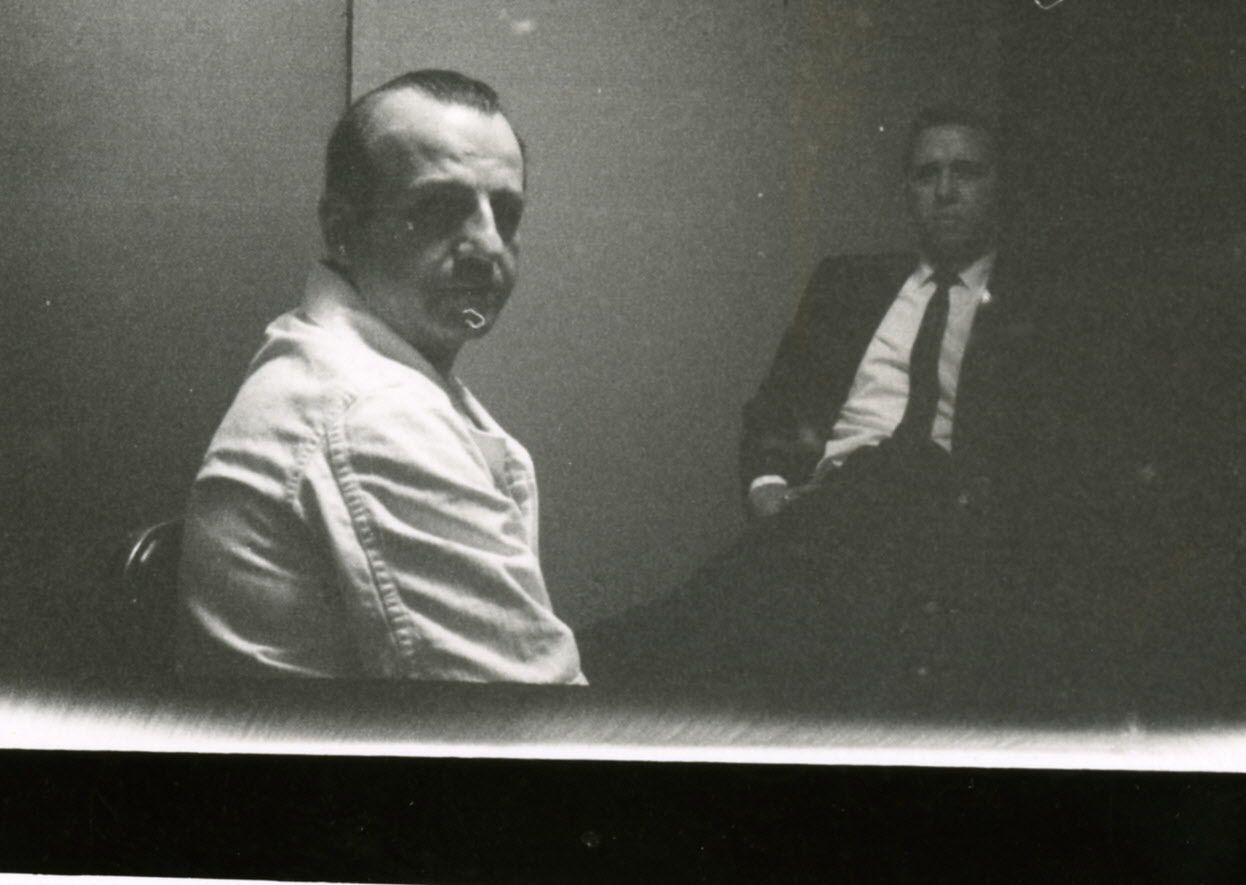 Black and white photograph of Jack Ruby in his jail cell at the Dallas County Jail in 1964, taken by his brother Earl Ruby. Lawyer Phil Burleson is visible in the background.
