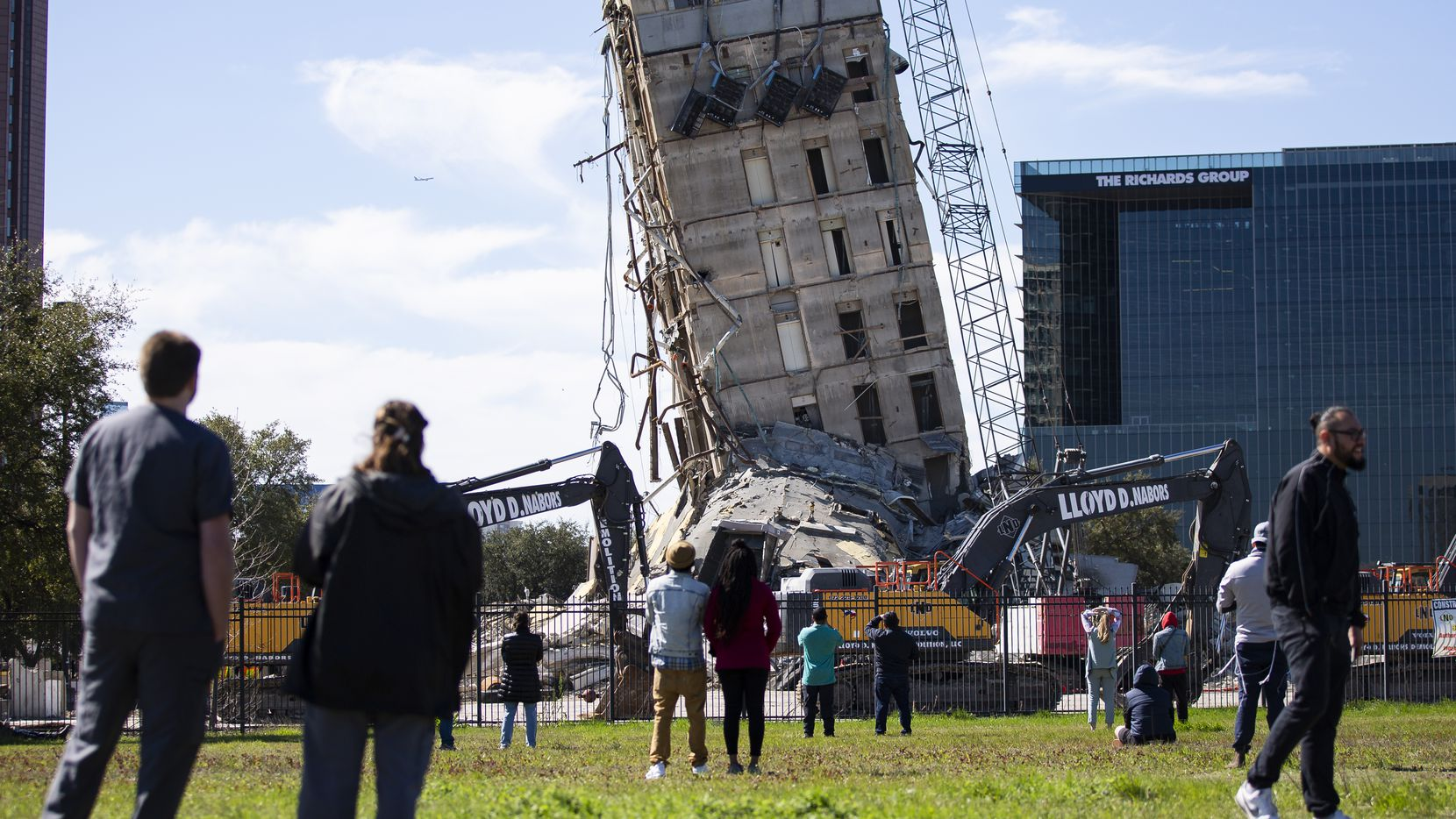 A crowd watches as a wrecking ball chips away at the top levels of the former Affiliated Computer Services building with a wrecking ball on Monday, Feb. 24, 2020 in Dallas.