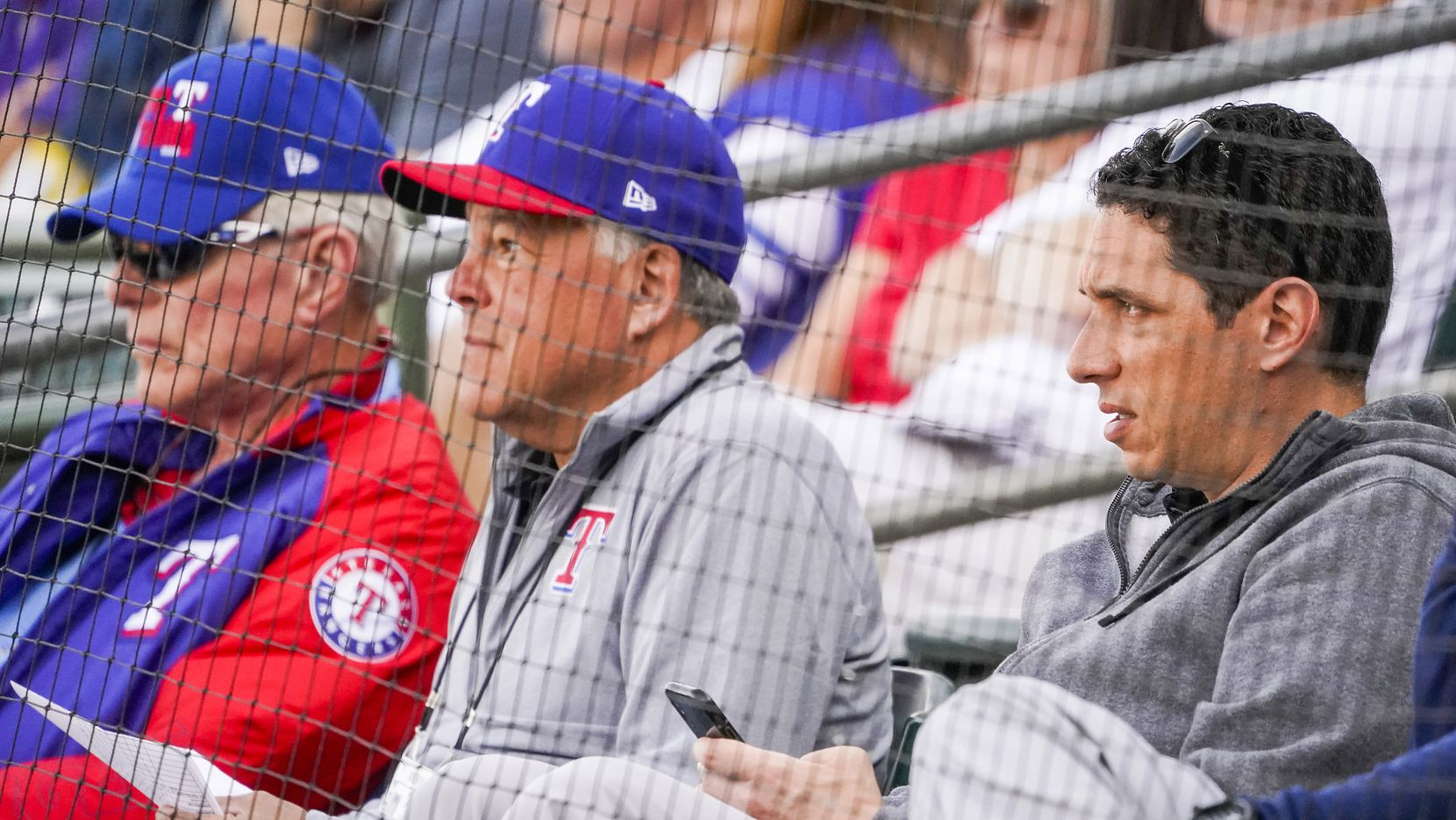 Texas Rangers general manager Jon Daniels (right) watches with co-chairman and managing partner Ray C. Davis (left) and chairman, ownership committee and chief operating office Neil Leibman (center) during the third inning of a spring training game against the Chicago Cubs at Surprise Stadium on Thursday, Feb. 27, 2020, in Surprise, Ariz.
