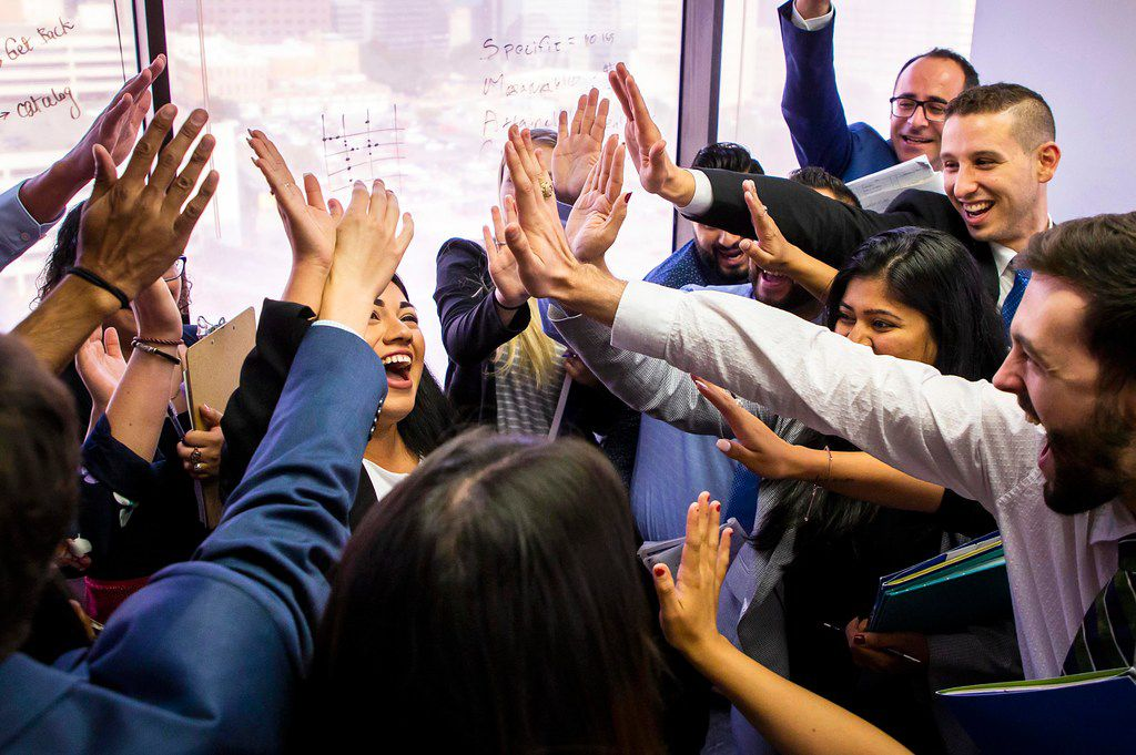 Leyla Cortez (center) got high-fives from the rest of the marketing team after she was recognized during a team meeting at CAM Partners.
