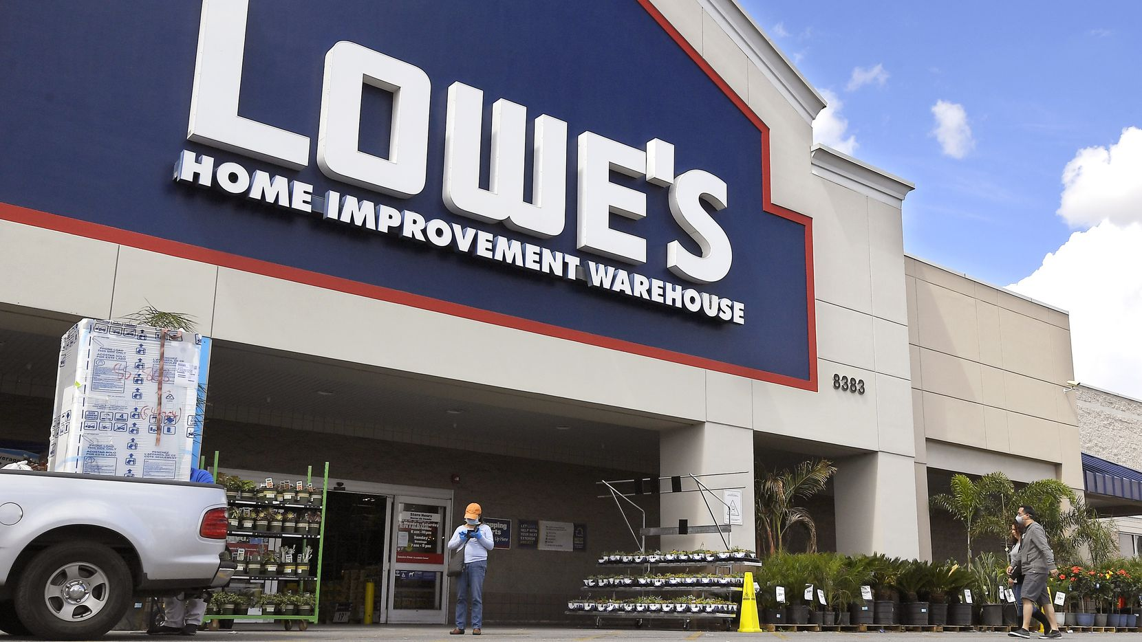 In this March 22, 2020 file photo, customers wearing masks walk into a Lowe's home improvement store in the Canoga Park section of Los Angeles. A spokesman for the company said it was opening an outlet store in Irving later this year.