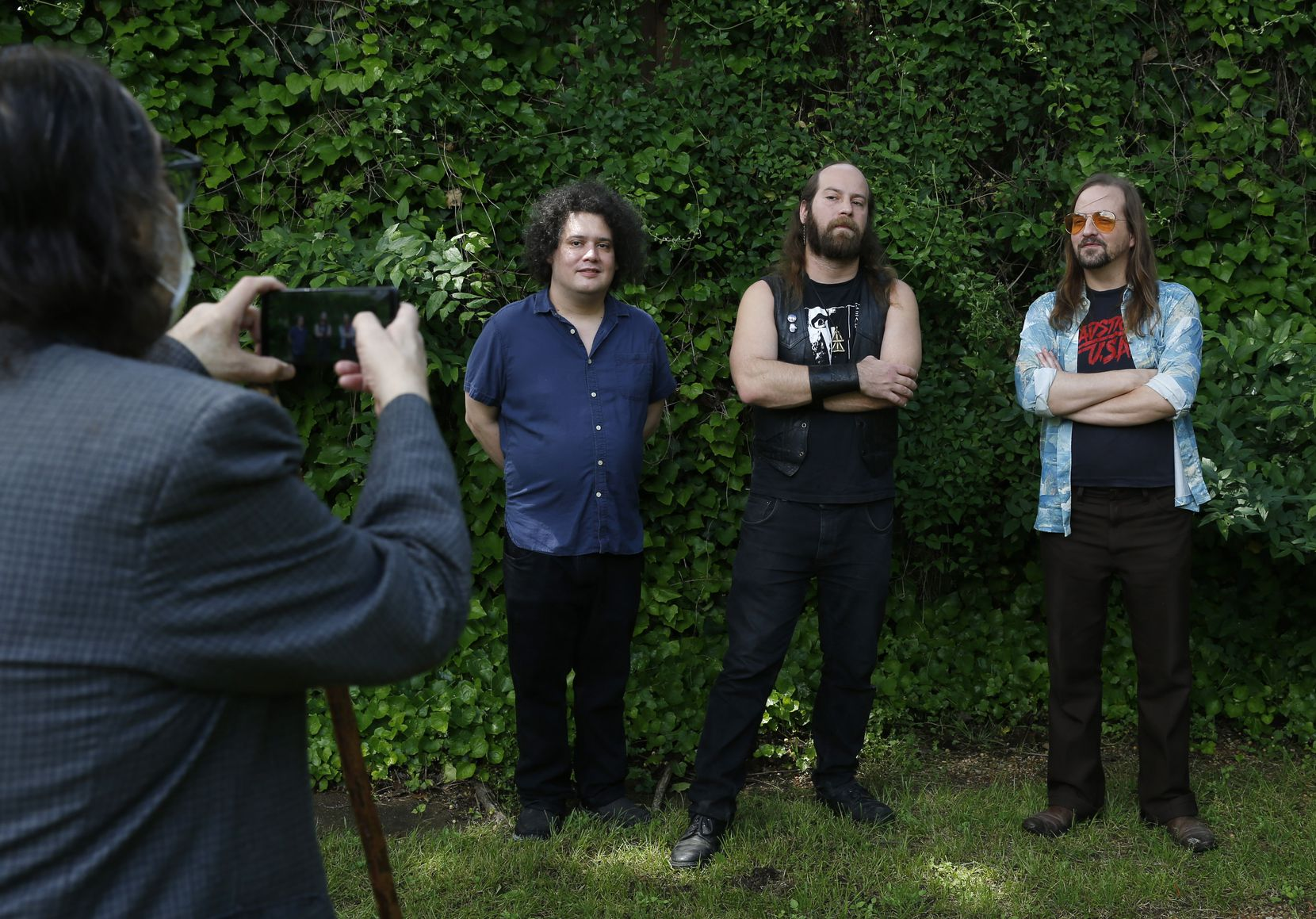 Dennis Gonzalez takes a photo of Aaron Gonzalez, Stefan Gonzalez and Daron Beck after a photo shoot in the backyard of his house in Dallas on Tuesday, April 28, 2020. Yells at Eels and Pinkish Black recorded an album together while members from both groups had life-threatening health issues.