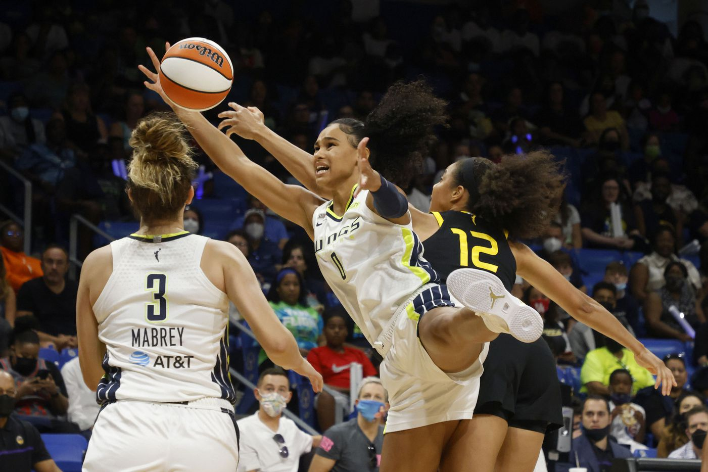 Dallas Wings forward Satou Sabally (0) grabs the ball in front of Los Angeles Sparks forward Nia Coffey (12) as Dallas Wings guard Marina Mabrey (3) looks on, during the first half of a WNBA basketball game in Arlington, Texas on Sunday, Sept. 19, 2021. (Michael Ainsworth/Special Contributor)
