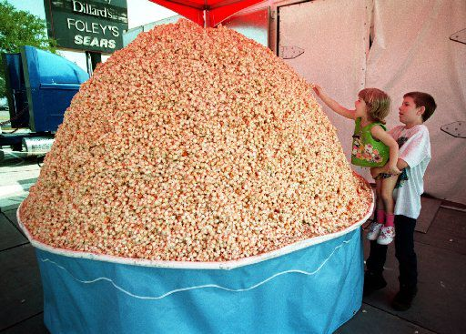 Amanda Adams got a little help from her  big brother Kyle Adams to place some popcorn onto the world's largest popcorn ball. The ball was at Valley View for area  boy scouts and cub scouts to add to it. Dallas was one of 50  stops in the U.S. and Canada. At this point the ball is estimated to weigh 6,000 pounds.