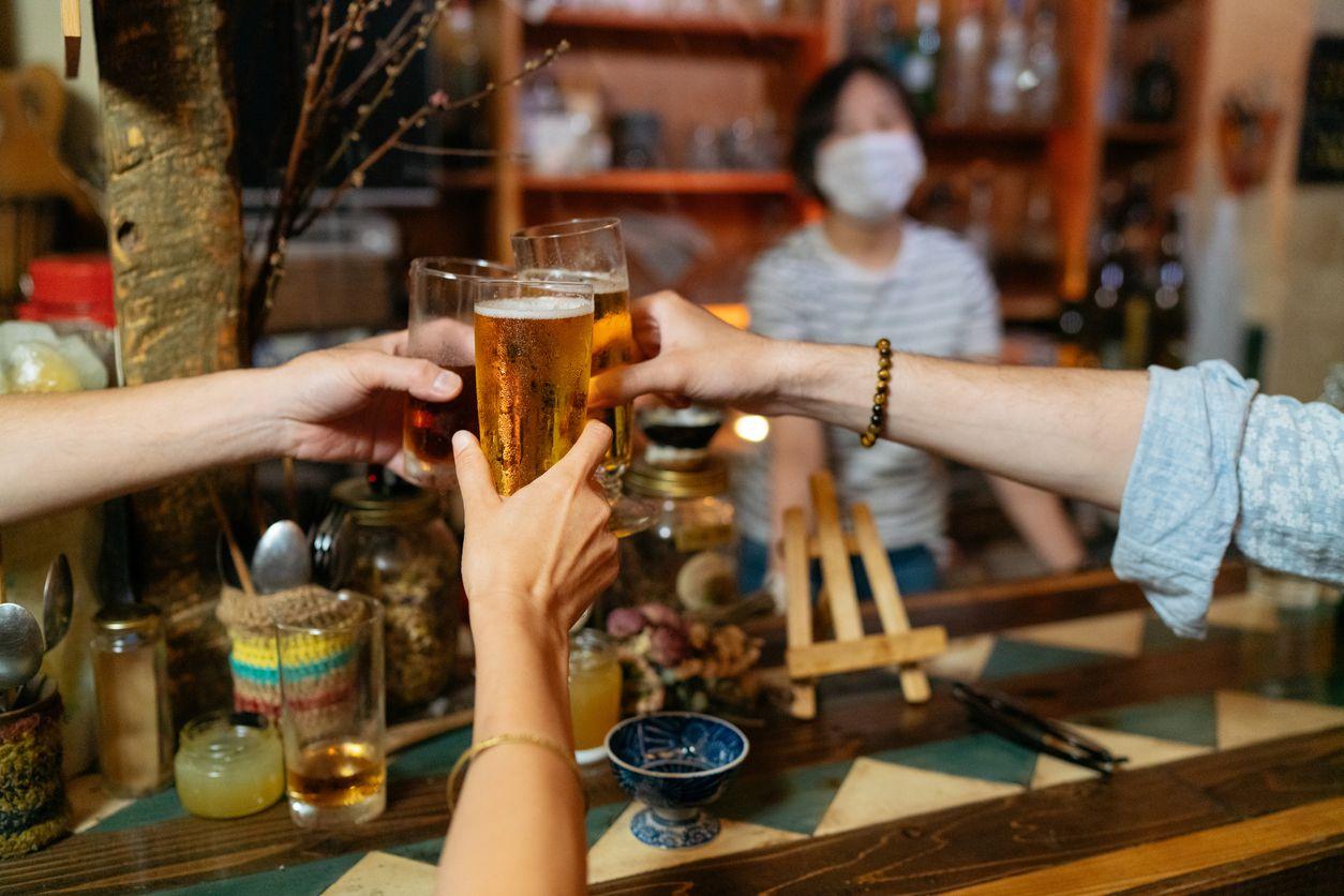 Foto de primer plano de personas que animan con cerveza en bar con medidas de protección de la prevención de covid.19.