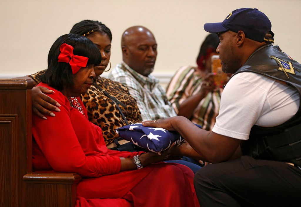 Patriot Guard Ernest Walker hands over the American flag to Daisy Garner, wife of civil rights activist Willie B. Ludden Jr., during his memorial service and wake Tuesday night.